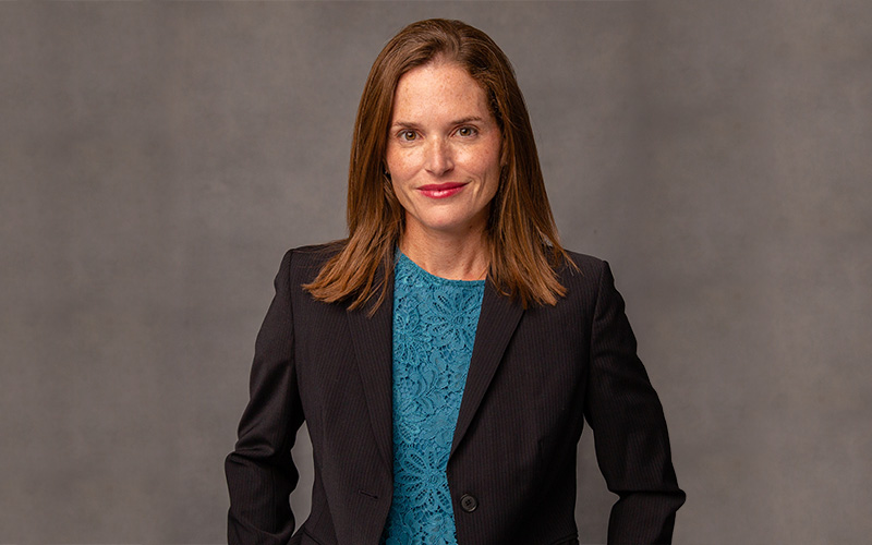 Dr. Andrea Bowers from Burlington County Orthopaedic Specialists wearing a teal blouse and dark gray fitted blazer smiling with a mottled gray photographer's background