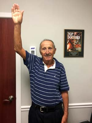 Patient raising hand after shoulder replacement surgery
