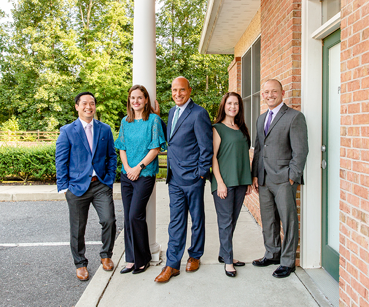 Group of healthcare practitioners standing casually outside of building