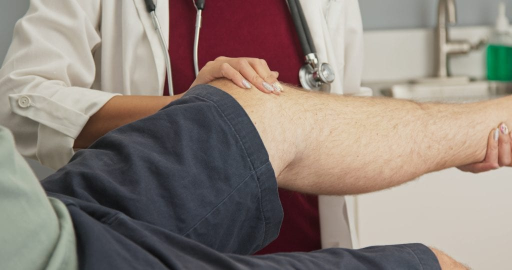Doctor examining knee of patient